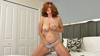 Redheaded Andi James has huge tits and likes to play with her cunt